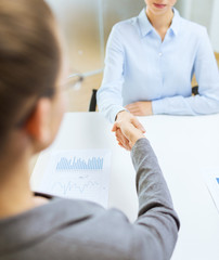 two calm businesswoman shaking hands in office