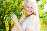 Portrait of beautiful blonde girl with yellow flowers