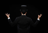 magician in top hat showing trick from the back