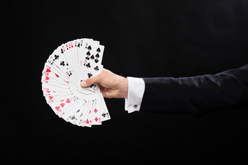 close up of magician hand holding playing cards