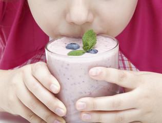 Child drinking blueberry yogurt