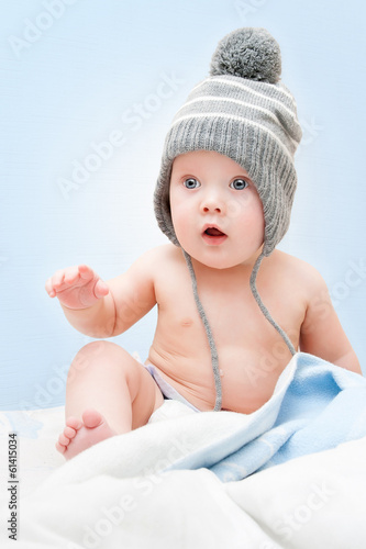 Beautiful baby in the cute hat with pompom