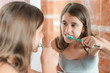 Girl brushing her teeth in front of a mirror