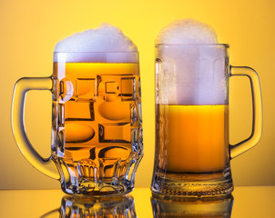 Two Mugs of fresh beer with cap of foam