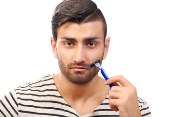 Man styling beard with concentration
