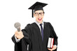 Young man in graduation gown holding a microphone and books
