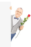 Senior gentleman standing behind panel and holding a red rose