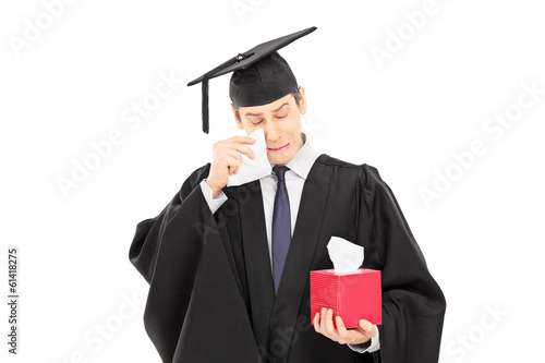 Sad young man in graduation gown holding box of wipes