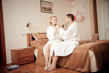 Man and woman drinking coffee in the morning in bed.