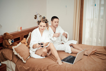 young couple working on the computer in bed