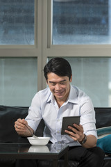 Asian Businessman eating breakfast and reading his tablet.