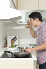 Asian man in kitchen making food for dinner.