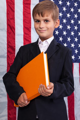 Ñute schoolboy is holding a book against USA flag