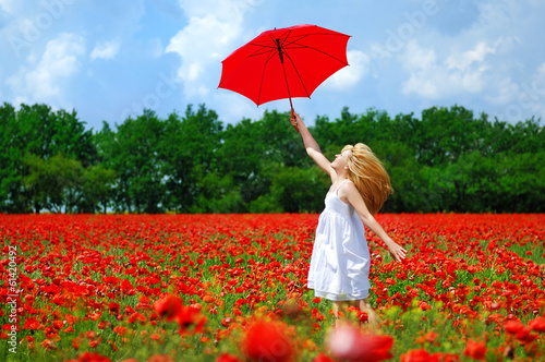happy girl jumping with the red umbrella over the poppy field