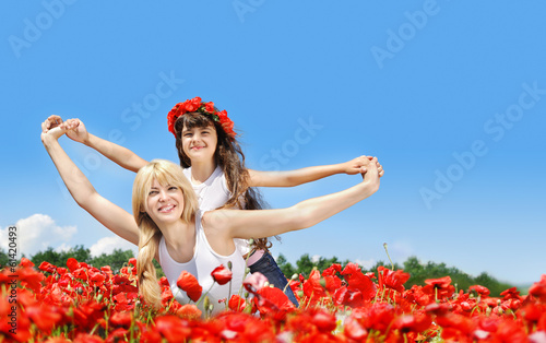 Mother with daughter  in a poppy field