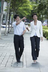 Two of Asian business colleagues walking in street