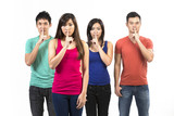 Group of Chinese friends with fingers over lips.