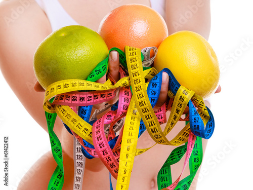 Fit woman with measure tapes fruit. Time for diet slimming.