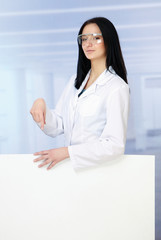 Woman doctor standing near blank