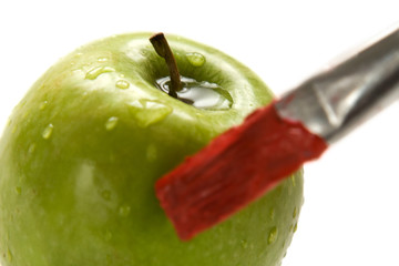 paintbrush painting a fresh green apple