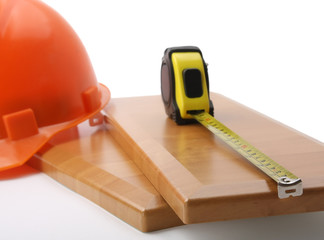 An orange hardhat with a ruler on wooden planks.