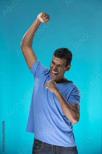 Indian man celebrating with his arm up.