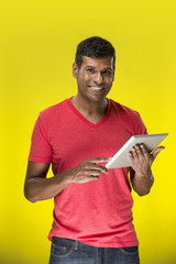 Indian man using a tablet PC In front of Yellow background.