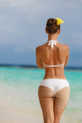 Sexy sandy woman buttocks on tropical beach background ocean