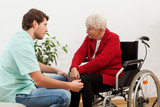 Doctor talking with disabled patient