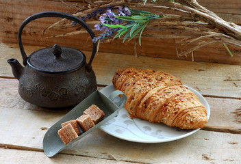 Croissant with sugar and teapot