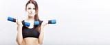 Young fit woman training with dumbbells
