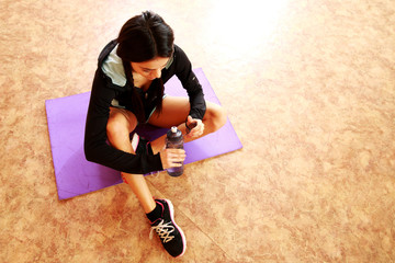 Young fit woman sitting on the yoga mat