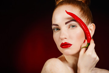 Portrait of beautiful red-haired woman with red hot chili pepper