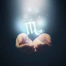 Les mains des femmes d'ouvrir à la lumière et la tenue signe du zodiaque pour Scorpi