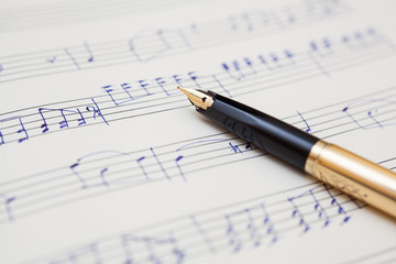 pen and music sheet with handwritten notes