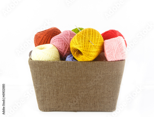 Heap of colorful yarn in basket on white background
