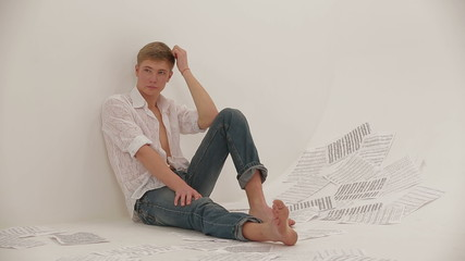 Young man seating on the floor in the studio