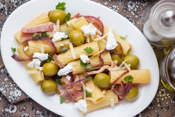 Rigatoni pasta with bacon, green olives, feta cheese, red onion