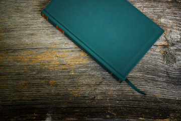 Green book on a textured wood background