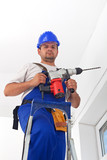 Worker with power drill standing on ladder