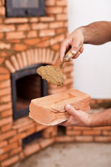 Masonry worker hands with brick and clay mortar on trowel
