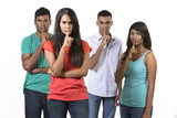 Group of Indian friends with fingers over lips.