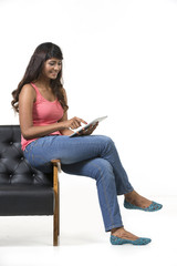 Young woman sitting on chair using a Digital Tablet PC.
