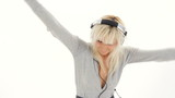 Beautiful woman listening to music in headphones and dancing