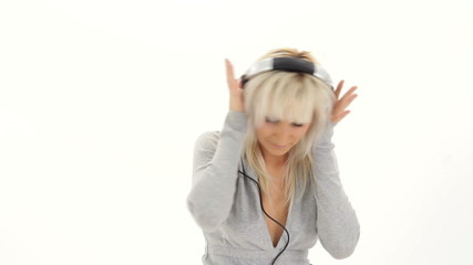 Young woman listening music in headphones and dancing