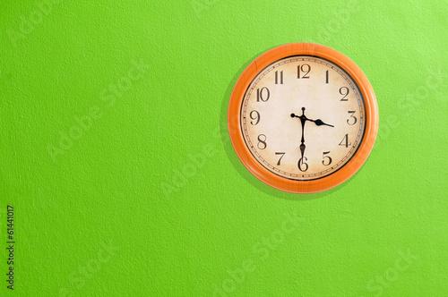 Leinwanddruck Bild Clock showing 03:30 on a green wall