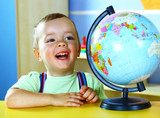 Smiling boy studying a globe