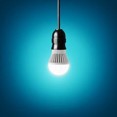 Glowing led bulb on blue background