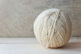 White ball of yarn on a wooden table over vintage wallpaper