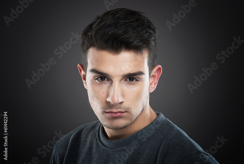 Serious young man looking at camera, dark background